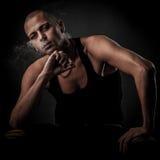 Den stiliga unga mannen röker cigaretten i mörker - fotografi av Royaltyfri Fotografi