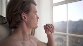 Den stiliga unga mannen som ser fundersamt eftertänksamt på sjösidabakgrund, fokuserade säkert Grabben med en naken torso reflekt