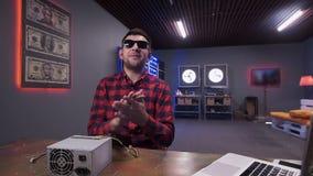 Den stiliga unga mannen talar på kamerainnehavasken av strömförsörjning med kylare arkivfilmer