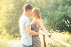 Den stiliga unga pojken med mörkt hår kysser flickan med långt blont hår Förälskat near träd för par royaltyfri foto