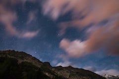 Den stjärnklara himlen med färgrika moln för suddig rörelse och ljust månsken Expansivt nattlandskap i de europeiska fjällängarna Royaltyfria Foton