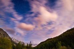 Den stjärnklara himlen med suddiga rörelsemoln och ljust månsken som fångas från skogsmark för lärkträd Expansivt nattlandskap i  Arkivbilder
