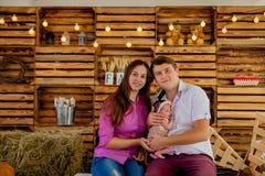 Den stolta modern och fadern som ler på deras nyfött, behandla som ett barn dottern på studion Royaltyfri Bild