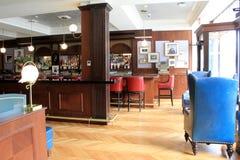 Den stora öppna foajén med antikviteten presiderar och bordlägger att leda in i stången, det Adelphi hotellet, Saratoga Springs,  arkivfoto