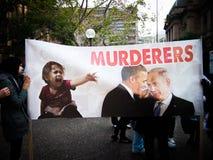 Den stora affischen för person som protesterarshowen säger `-mördare` med bild av presidenten Obama och Israel presidenter Arkivfoto