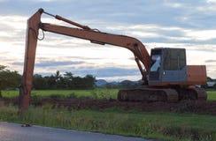 Den stora backhoegrävskopamaskinen i den gröna risfältet Arkivfoton