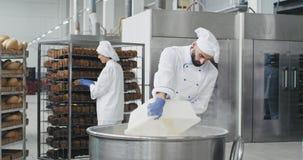 Den stora bagaren för bageribransch förbereder degen tillfogar mjölet i stora arbetare för en behållarebakgrund för att ordna brö arkivfilmer