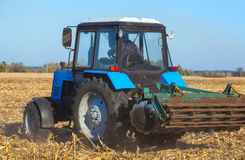 Den stora blåa traktoren plogar fältet och tar bort restna av föregående mejad havre royaltyfri fotografi