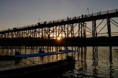 Den stora bron som gjordes av trä för att använda, korsade från en sida till en annan sida av floden och solnedgången Royaltyfri Foto