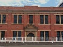 Den stora byggnaden för röd tegelsten bak det vita staketet royaltyfri foto