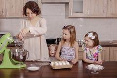 Den stora familjen - en moder och tre barn - två döttrar och en son, kock i köket, piskar krämen i en blandare royaltyfri bild