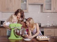 Den stora familjen - en moder och tre barn - två döttrar och en son, kock i köket, piskar krämen i en blandare royaltyfri foto