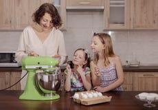 Den stora familjen - en moder och tre barn - två döttrar och en son, kock i köket, piskar krämen i en blandare arkivbilder