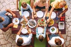 Den stora familjen har en matställe med nytt lagat mat mål på öppen trädgård t arkivbild