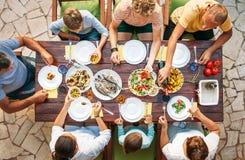 Den stora familjen har en matställe med nytt lagat mat mål på öppen trädgård t royaltyfria foton