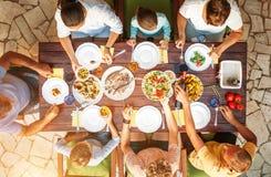 Den stora familjen har en matställe med nytt lagat mat mål på öppen trädgård t royaltyfri bild