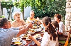 Den stora familjen har en matställe på trädgårds- terrass royaltyfria foton