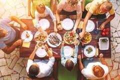 Den stora familjen har en matst?lle med nytt lagat mat m?l p? ?ppen tr?dg?rds- terrass arkivbild