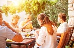 Den stora familjen har matställen på öppen trädgårds- terrass arkivbild
