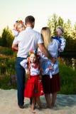 Den stora familjen i de etniska ukrainska dräkterna sitter på ängen, begreppet av en stor familj tillbaka sikt royaltyfria foton