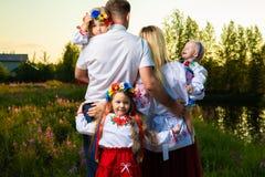 Den stora familjen i de etniska ukrainska dräkterna sitter på ängen, begreppet av en stor familj tillbaka sikt arkivfoto