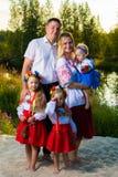 Den stora familjen i etniska ukrainska dräkter sitter på ängen, begreppet av en stor familj arkivfoton