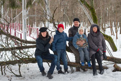 Den stora familjen sitter på trädstammen i vinterskog Royaltyfria Bilder