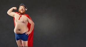 Den stora feta nakna mannen i en superherodräkt visar musklerna på högt Fotografering för Bildbyråer