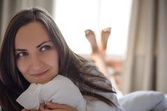 Den stora frontal ståenden av en ung kvinna i sängotta, vaknar upp, den bra morgonen, kopieringsutrymme royaltyfria bilder
