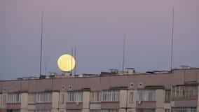 Den stora fullmånen ovanför taket av en flervånings- byggnad flyttar sig upp stock video