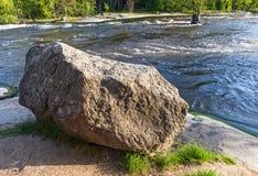 Den stora granitstenen lägger på en flodkust Arkivfoto