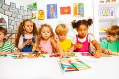 Den stora gruppen av ungar spelar med att modellera lera arkivfoto