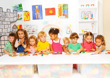 Den stora gruppen av ungar spelar med plasticine i grupp Fotografering för Bildbyråer