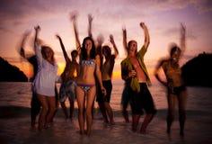Den stora gruppen av ungdomarsom tycker om en strand, festar royaltyfria bilder