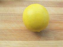 Den stora gula citronen ligger på en blå platta på en gul bakgrund Fotografering för Bildbyråer