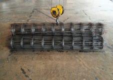 Den stora gula kroken av kranen lyfter upp trådingreppet Arkivfoton