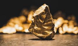 Den stora guld- klumpen framme av en kulle av guld - finansiera begreppet Royaltyfri Fotografi