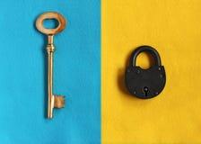 Den stora guld- tangenten på blå filt och stänger hänglåset på gul filt Arkivbilder
