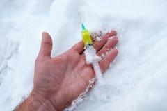 Den stora håriga handen i snön, en man som bär en injektionsspruta men, bar inte arkivfoton