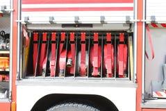 den stora lastbilen för röd brand vattnar med slang stridighetservice i brandlastbil Royaltyfria Bilder