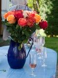 Den stora ljusa buketten av rosor i en blå tillbringare står på tabellen i trädgården Arkivbilder