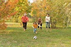 Den stora lyckliga familjen som spelar fotboll i höst, parkerar arkivfoton