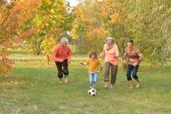 Den stora lyckliga familjen som spelar fotboll i höst, parkerar royaltyfri fotografi