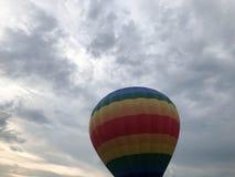 Den stora mång--färgade ljusa runda regnbågen färgade den randiga randiga flygballongen med en korg mot himlen i aftonen royaltyfria foton