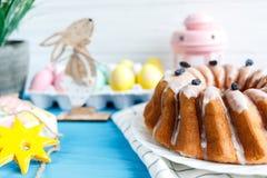 Den stora plattan med kakan och handen målade färgrika ägg, på handduken på blå bakgrund close upp garnering easter arkivfoton