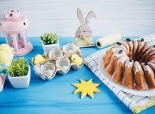 Den stora plattan med kakan och handen målade färgrika ägg, på handduken på blå bakgrund close upp garnering easter royaltyfri foto