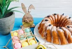 Den stora plattan med kakan och handen målade färgrika ägg, på handduken på blå bakgrund close upp garnering easter royaltyfri bild
