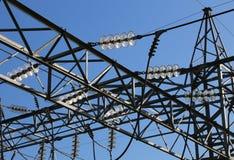 Den stora pylonen av hög spänning kablar med den blandade glass isolatorn royaltyfri bild