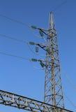 Den stora pylonen av hög spänning kablar med den blandade glass isolatorn arkivbild