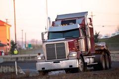 Den stora röda halva lastbilen vänder på huvudvägrampen Arkivfoton